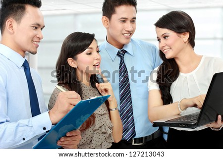 group of happy business people doing presentation with laptop during meeting