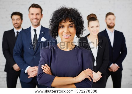 Group of happy business people standing in office with female leader at front - stock photo