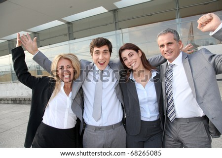 Group of happy business people standing outside - stock photo