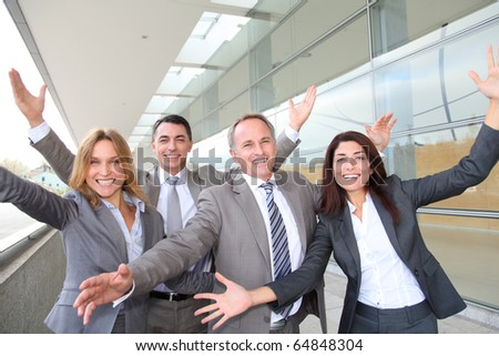 Group of happy business people with arms up - stock photo