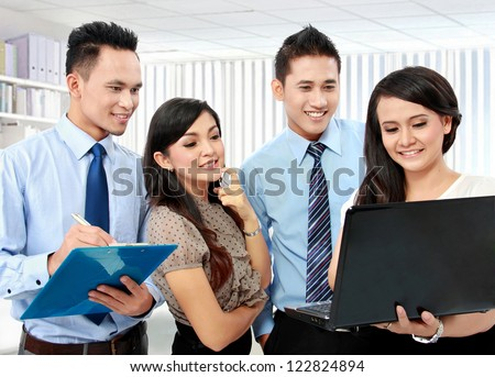 group of happy business people working on laptop during meeting