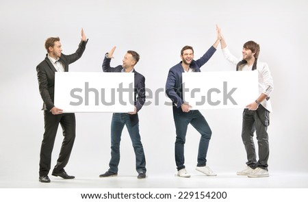 Group Of Happy Businessmen Holding Blank Placard - stock photo
