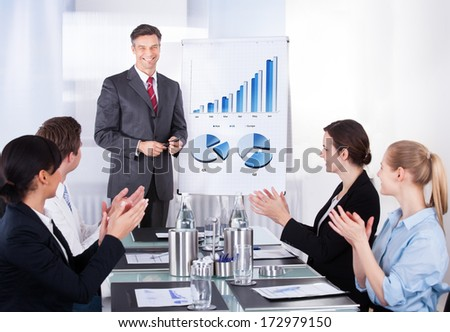 Group Of Happy Businesspeople Appreciating Businessman At Conference - stock photo