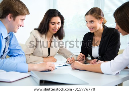 Group of happy businesspeople in a meeting at office