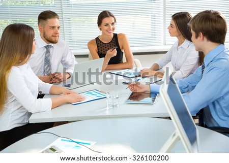Group of happy businesspeople in a meeting at office - stock photo