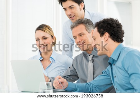 Group Of Happy Businesspeople In Office Looking At Laptop