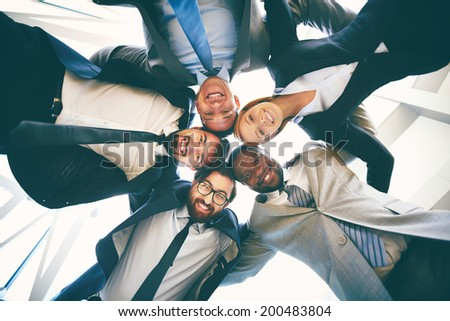 Group of happy businesspeople in suits standing head to head - stock photo