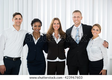 Group Of Happy Businesspeople Standing In Office