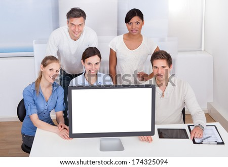 Group Of Happy Businesspeople With Blank Computer On Desk - stock photo