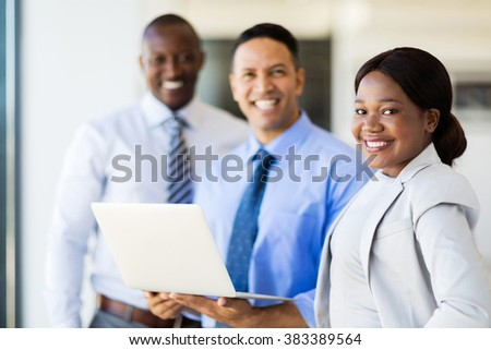 group of happy businesspeople with laptop computer - stock photo