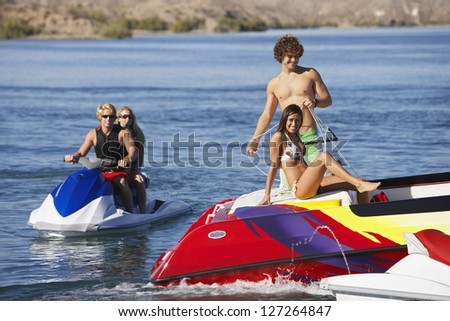 Group of happy caucasian friends on boats at lake