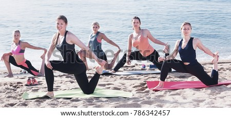 Group of  happy cheerful positive females performing yoga on sunny seaside