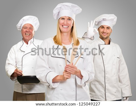 Group Of Happy Chef's At Work On Grey Background