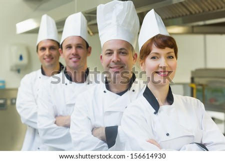 Group of happy chefs smiling at the camera in a kitchen wearing uniforms - stock photo