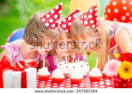 Group of happy children celebrating birthday. Kids having fun in spring garden - stock photo