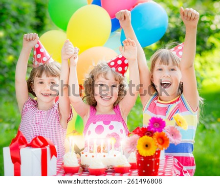 Group of happy children celebrating birthday. Kids having fun in spring garden - stock photo