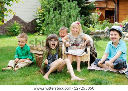 Group of happy children having picnic on a green lawn in front of country house - stock photo