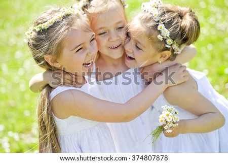Group of happy children on green grass outdoors in spring park - stock photo