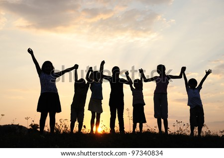 Group of happy children playing at summer sunset