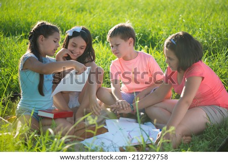Group of happy children playing on green grass