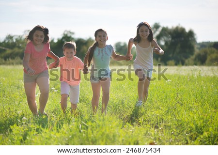 Group of happy children playing on meadow