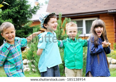 Group of happy children playing outdoors in front of country house - stock photo