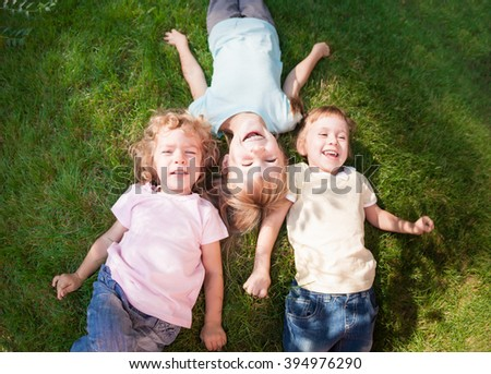 Group of happy children playing outdoors in spring park. Top view portrait - stock photo