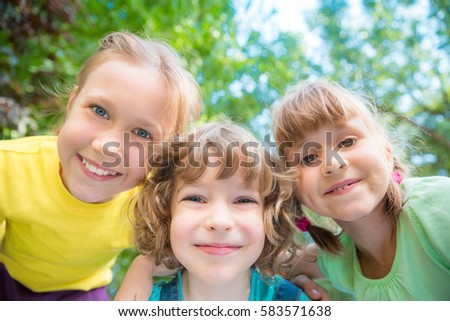 Group of happy children playing outdoors. Kids having fun in spring park. Low angle view portrait