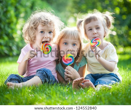 Group of happy children sitting on green grass in spring park - stock photo