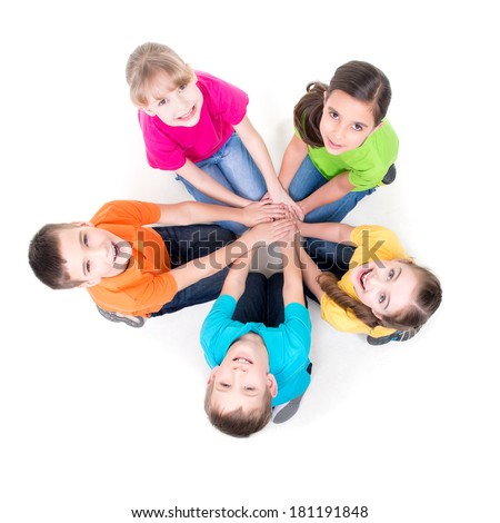 Group of happy children sitting on the floor in a circle holding hands and looking up - isolated on white. - stock photo