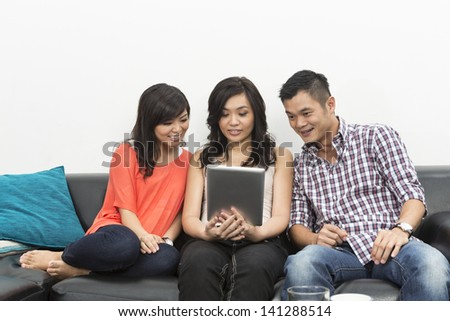 Group of Happy Chinese friends hanging out together at home using Digital Tablet - stock photo