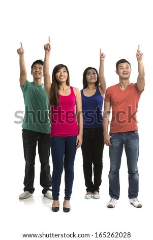 Group of happy Chinese friends pointing upwards. Isolated on a white background.