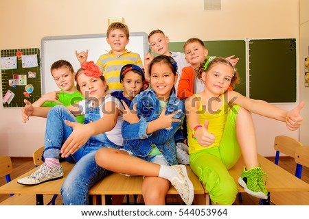 Group of happy classmates in bright casual clothes posing together at a classroom. Education.