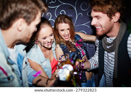 Group of happy clubbers with champagne toasting at party