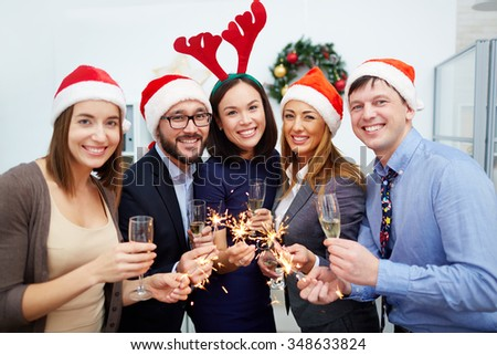Group of happy colleagues with champagne and Bengal lights looking at camera - stock photo