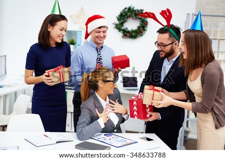 Group of happy employees making Christmas surprise to their colleague