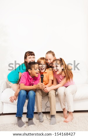 Group of happy exited diversity looking kids, boys and girls, singing together sitting on the coach in living room