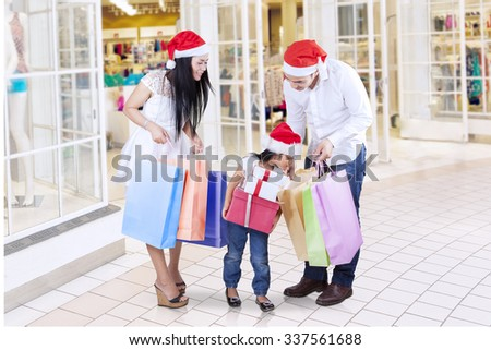 Group of happy family holding shopping bags and christmas gifts, looking at shopping bags in the shopping center - stock photo