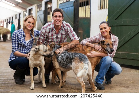 group of happy farm workers with pet dogs in stables - stock photo