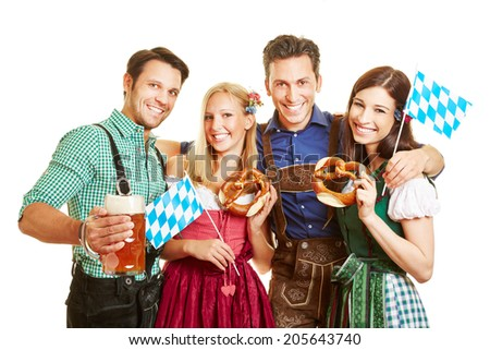 Group of happy friends celebrating Oktoberfest with beer and pretzel in Bavaria