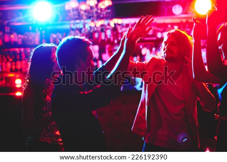 Group of happy friends dancing in nightclub - stock photo