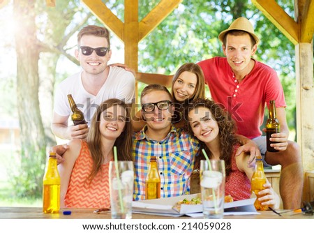 Group of happy friends drinking and having fun in pub garden - stock photo