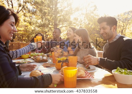 Group of happy friends eat and drink at a table at a barbecue - stock photo