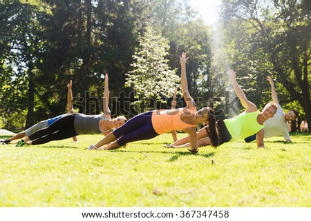 group of happy friends exercising outdoors - stock photo