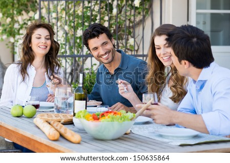 Group Of Happy Friends Having Dinner At Patio - stock photo