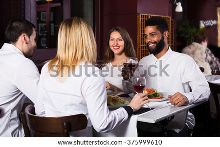 Group of happy friends having dinner in restaurant and laughing. Focus on caucasian man