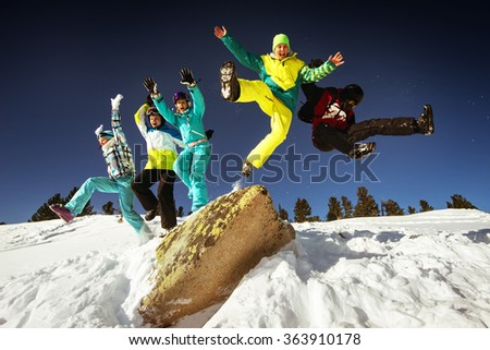 Group of happy friends having fun jumping from big rock to snow. Ski and snowboard resort Sheregesh, Siberia, Russia - stock photo