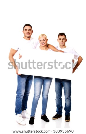 Group of happy friends holding empty banner - stock photo