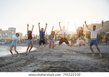 Group of happy friends jumping on beach
