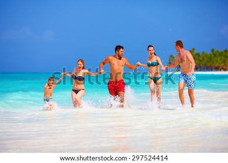 group of happy friends running together on tropical beach